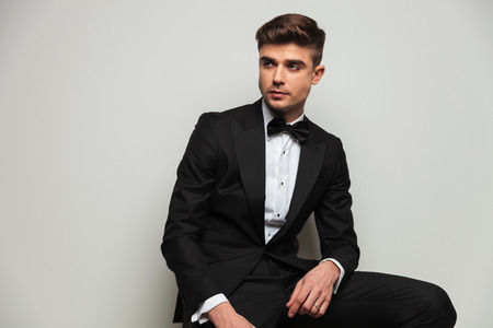 portrait of curious elegant man wearing black tuxedo looking to side while sitting on wooden chair on light grey background