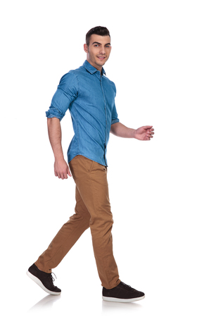 side view of handsome casual man wearing blue shirt walking on white background, full body picture