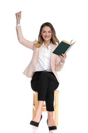 excited businesswoman in pink suit celebrates with hand in the air while holding book and sitting on wooden chair on white background