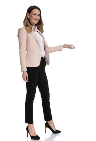 young businesswoman in high heels presents to side while standing on white background, full length picture
