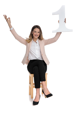 businesswoman sits on chair on white background and celebrates first place with hands in the air 版權商用圖片