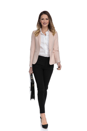 attractive businesswoman holding briefcase and wearing high heels walks forward on white background, full body picture 版權商用圖片