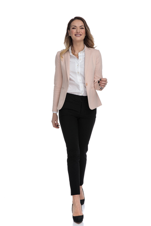 sexy businesswoman wearing pink suit and high heels walking forward and smiling on white background, full body picture Imagens