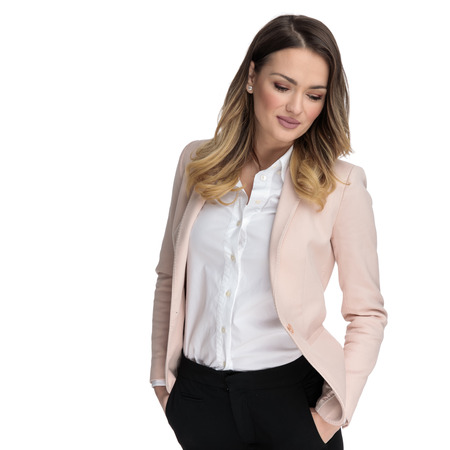 relaxed businesswoman wearing undone pink suit and shirt looks down to side while standing on white background, portrait picture