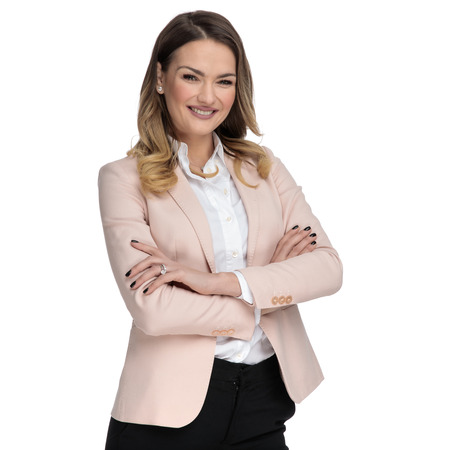 confident businesswoman wearing pink suit stands on white background with arms folded, portrait picture
