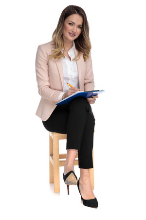 attractive businesswoman sits on wooden chair on white background and writes on blue clipboard, full body picture 版權商用圖片