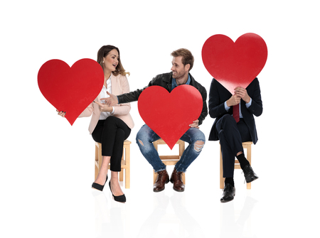3 seated people holding big red hearts are sharing the love on white background 版權商用圖片