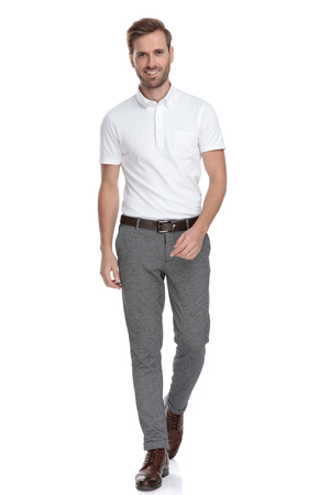 confident young casual man is walking forward on white background Stock fotó