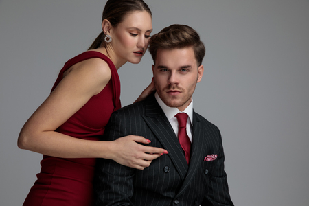 seated elegant man with his woman behind him, posing on grey background