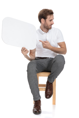 seated casual man holding a speech bubble and showing it to someone to his side on white background