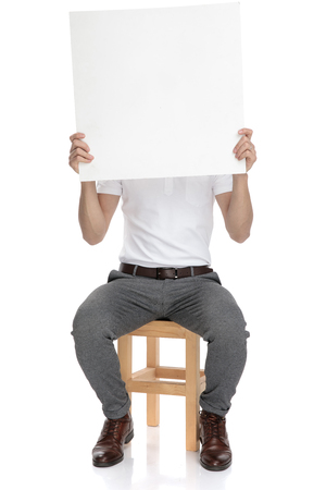 casual man covers his face with a blank board on white background Foto de archivo - 117534596