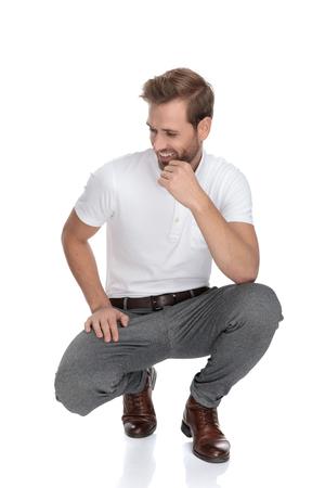 Lughing accovacciato uomo casual intelligente pensa e guarda di lato dalla telecamera su sfondo bianco