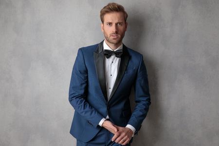 Hombre elegante vestido con un esmoquin azul tomados de la mano con una leve sonrisa en su rostro sobre un fondo gris claro