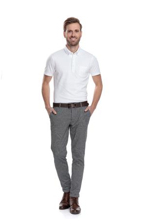 uomo casual fiducioso felice in piedi con le mani in tasca su sfondo bianco Archivio Fotografico