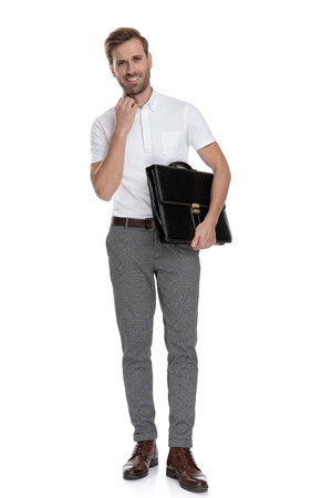 smiling young casual man holding briefcase and adjusts his collar on white background