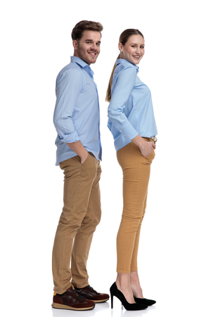 side view of smiling man and woman with hands in pockets standing on white background, full body picture