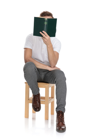 casual man sitting and reading a book covering his face with it on white background
