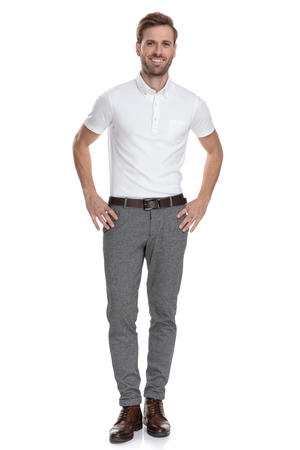 happy young smart casual man with hands on waist standing on white background