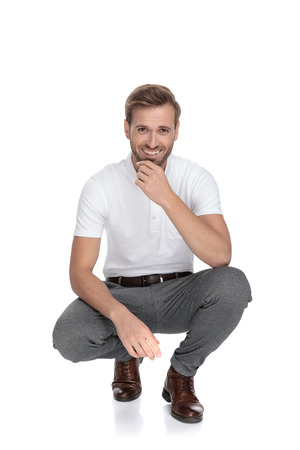 crouched smiling casualm man is thinking on white background Banque d'images - 117535613