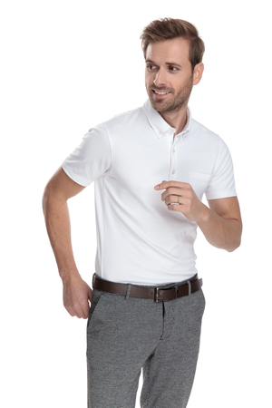 l'uomo casual sorridente che si aggiusta i pantaloni sembra a lato su sfondo bianco Archivio Fotografico