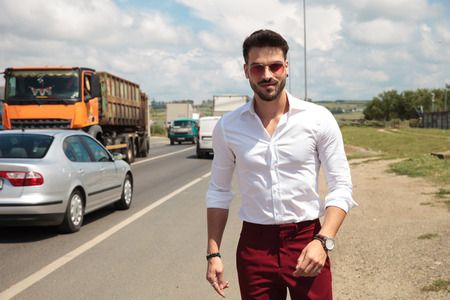 attractive man wearing sunglasses smiling and walking on the side of the road