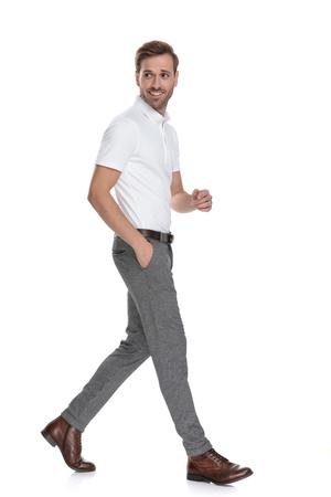 Sonriente hombre casual inteligente camina y mira hacia atrás sobre su hombro sobre fondo blanco. Foto de archivo