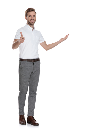full body picture of a smiling man presenting and making the ok thumbs up hand sign on white background Foto de archivo