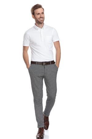 uomo curioso con le mani in tasca cammina e guarda di lato su sfondo bianco