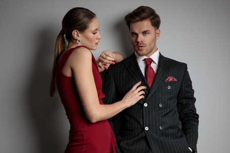 woman in red dress touching elegant man's chest on grey background