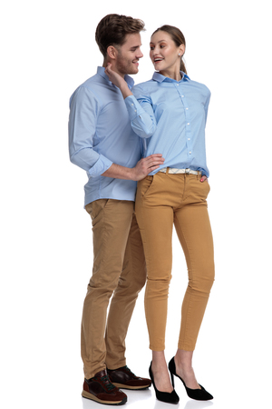 embraced casual man and woman looking at each other while standing on white background