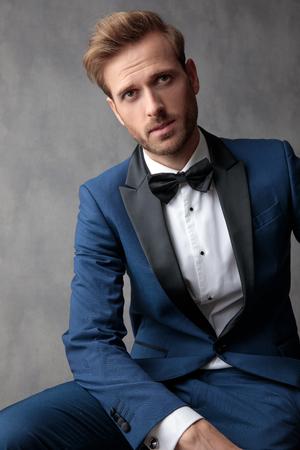 Hombre elegante sentado en una silla, pensando en algo, sosteniendo una mano sobre sus piernas sobre un fondo gris claro Foto de archivo