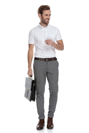 curious smart casual man holding suitcase looks to side on white background
