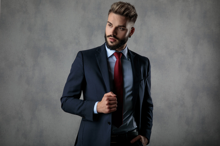 relaxed businessman holding suits collar and hand in pocket looks to side while posing in studio