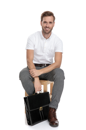 smiling young casual man sitts and holds briefcase down near his feet on white background Banco de Imagens
