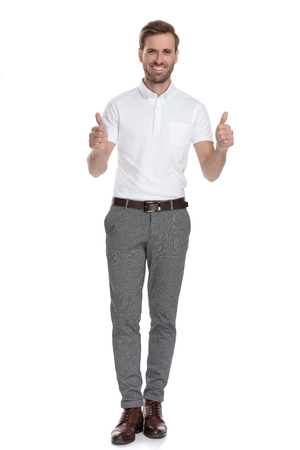 successful young smart casual man makes the ok thumbs up hand sign while standing on white background 免版税图像