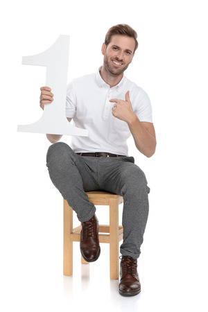 Seated casual man says he is number one by poiinting at himself on white background