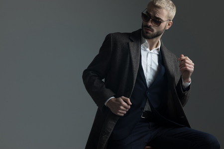 blonde guy with sunglasses adjusting his collar while looking away Фото со стока