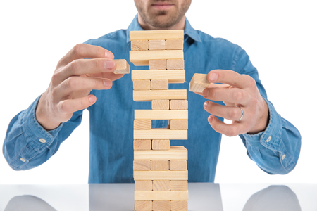 casual dressed man playing a game of wooden blocks, just removed simultaneously two bricks at a time Reklamní fotografie