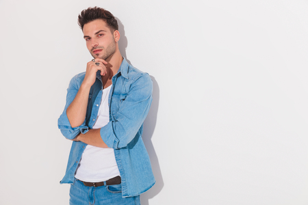 Attractive man holding his hand at his chin while looking at the camera on a light background