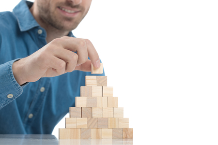 Casual dressed man placing very precisely a tiny wooden brick on top of a tower with his fingers Stock fotó