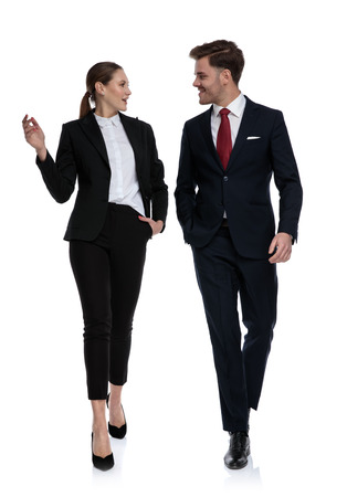 couple in business suits walking and talking while looking at each other on white background