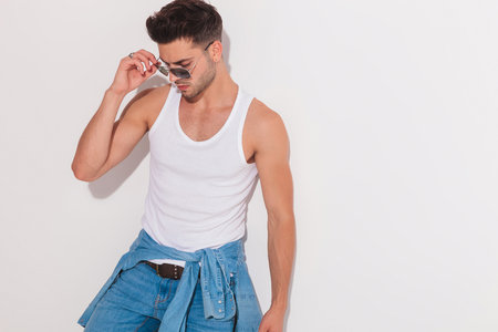 Attractive man wearing a white undershirt holding his shades while looking down to a side on a light background