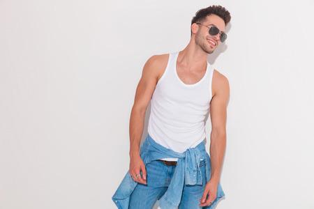 Hombre atractivo vistiendo su camisa atada alrededor de su cintura sonriendo mientras mira a un lado sobre un fondo claro