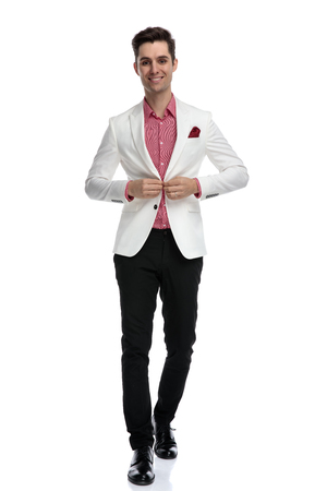 smiling elegant man buttoning his coat and walking on white background Banque d'images