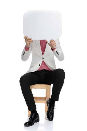 elegant businessman holding speech bubble over his face while sitting on chair on white background
