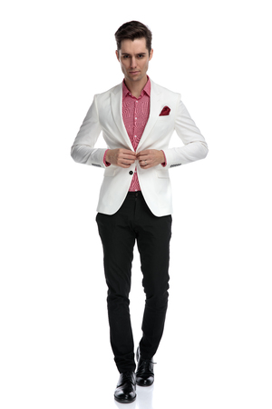 young cool elegant man walking and buttoning his coat on white background