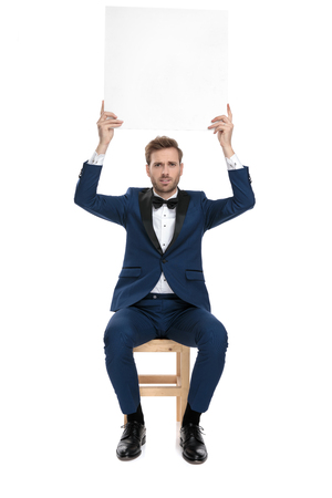 seated serious man in blue suit holding an empty billboard up in the air on white background