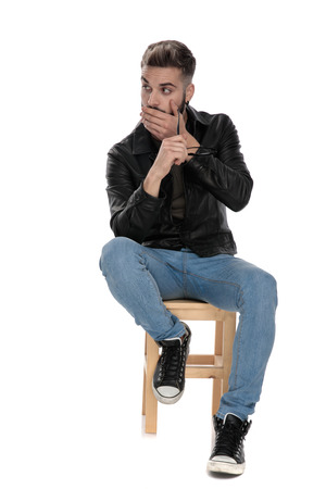 man in black jacket and blue jeans sitting on chair with hand at chin looking amazed on white background 写真素材