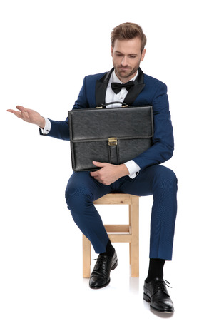 seated disappointed man in blue suit holds a black suitcase on his lap on white background