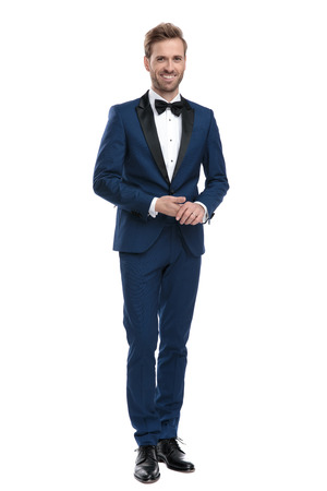 smiling man in blue suit holding his hands together while standing on white background Stock Photo